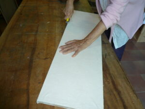 2 Jean in art studio cutting the paper canvas from the wooden frame