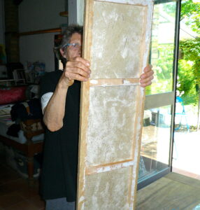 Jean Tori lifting wooden frame of the paper canvas