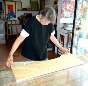Jean laying paper down on the first dried layer of paper