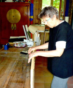 Jean pressing down paper on the wooden frame edges